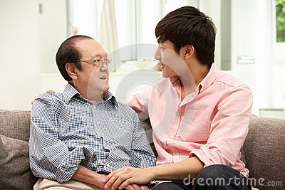 Chinese Father With Adult Son Relaxing At Home