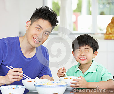 Chinese Father And Son Sitting At Home Eating