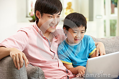 Chinese Father And Son Using Laptop