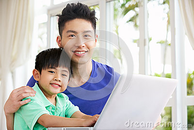 Chinese Father And Son Using Laptop At Home