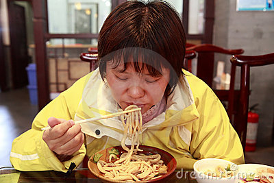 Chinese female eating noodles