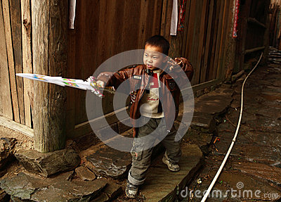 Chinese five year old boy playing with a plastic sword in the village street, editorial images. Editorial Image