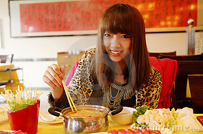 Chinese girl eating hot pot