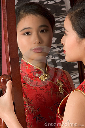 Chinese girl in red cheongsam by mirror