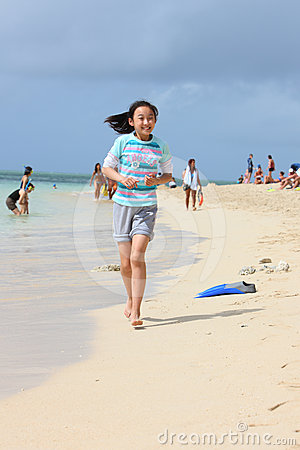 Chinese girl running on beach