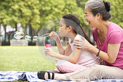 Chinese Grandmother With Granddaughter In Park