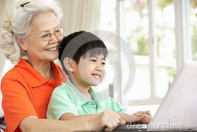 Chinese Grandmother And Grandson Using Laptop