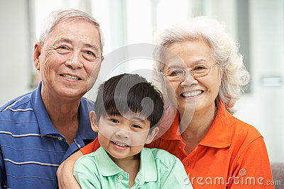 Chinese Grandparents With Grandson Relaxing At Hom