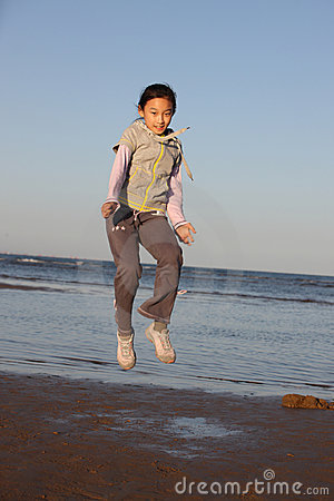 Chinese little girl jumping on the beach