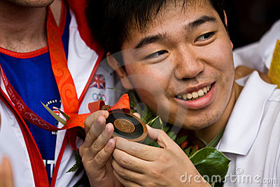 Chinese man holds Olympic medal Editorial Image