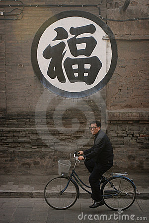 Chinese man riding a bike Editorial Image