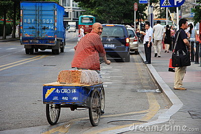 Chinese man riding a bike selling traditional cake Editorial Stock Image