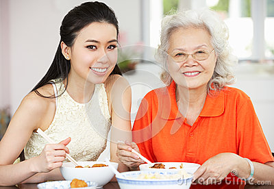 Chinese Mother And Adult Daughter Eating Meal