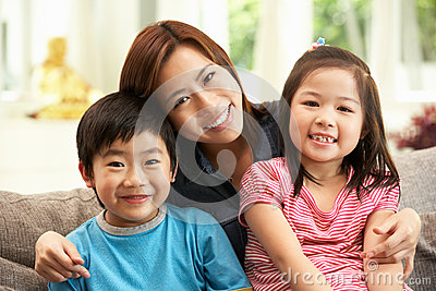 Chinese Mother And Children Sitting On Sofa