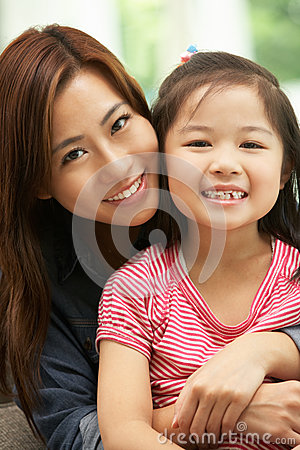 Chinese Mother And Daughter Sitting On Sofa