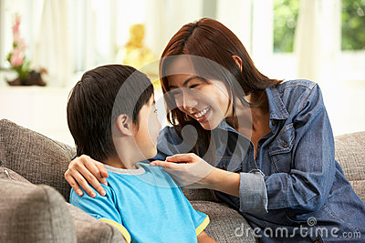 Chinese Mother And Son Sitting On Sofa