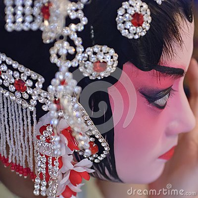 A chinese opera actress is painting her face
