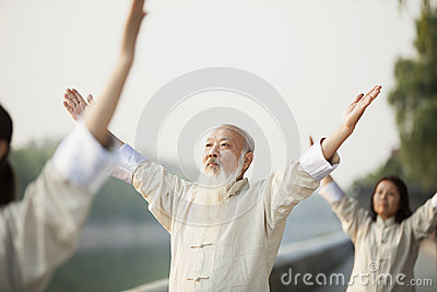Chinese People Practicing Tai Ji, Arms Raised, Outdoors