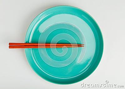Chinese style chopsticks put on green dish
