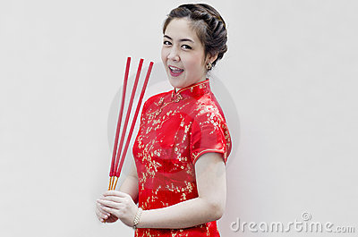 Chinese young woman holding joss sticks