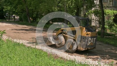 Skid steer loader moving sand soil at construction area outdoors stock video footage