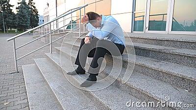 Chiuda su del responsabile triste di ribaltamento che si siede sulle scale vicino all'edificio per uffici ed a gridare Il giovane archivi video