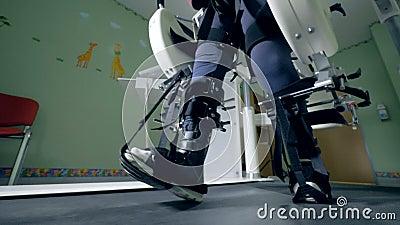 Chiuda su delle gambe di camminata legate con le cinghie di una macchina di simulazione archivi video