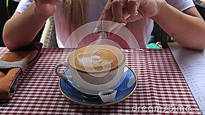 Chiuda su delle mani della donna che mettono lo zucchero su una tazza e su una corda di caffè, in un caffè archivi video
