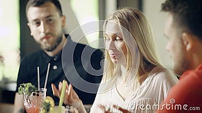 Chiuda su di bella ragazza che si siede al contatore della barra con due amici maschii Giovane donna che racconta una storia ai c stock footage