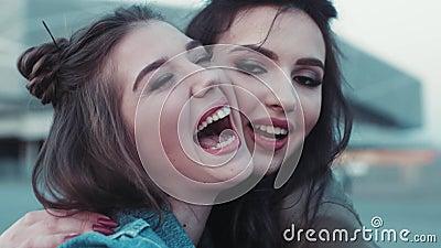 Chiuda su un punto di vista di due ragazze con bello trucco che impazzono, ridere, abbracciante Bellezza naturale, usura dei jean stock footage