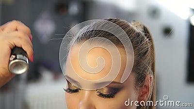 Chiuda sul colpo della lacca degli spruzzi del parrucchiere su un modello mentre fanno capelli-faccia Il parrucchiere fa l'acconc archivi video