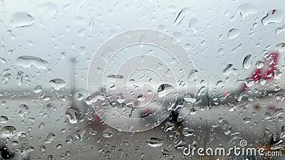 Chiudere il video 4k attraverso una finestra di aeroplano bagnato sul terminale dell'aeroporto e sugli aerei durante una tempesta archivi video