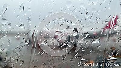 Chiudere il video 4k delle goccioline piovose che cadono su un portello di aeroplano bagnato in aeroplano archivi video