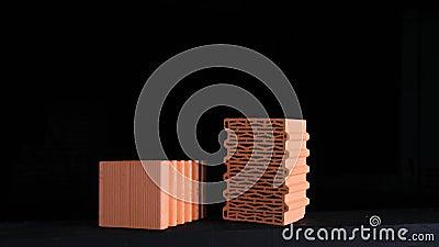 Chiusura di due mattoni rossi su fondo nero Riprese in borsa Dimostrazione di due blocchi di ceramica rossa con linee ondulate archivi video