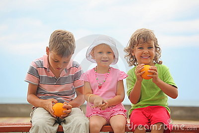 Chjildren with oranges sitting on wooden bench