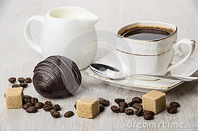 Chocolate cake, jug milk, pieces of sugar and coffee cup