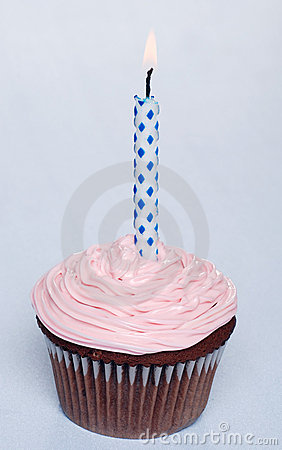 Chocolate cupcake with pink frosting and candle
