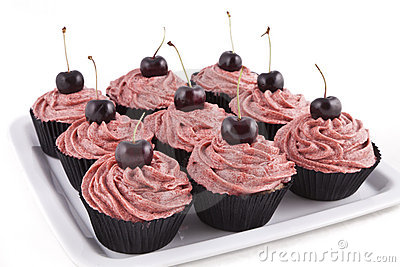 Chocolate cupcakes, with red frosting and a cherry