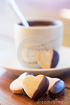Chocolate dipped heart shaped cookies and cup of coffee