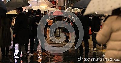 Chodz?cy ludzie przy Shibuya skrzy?owaniem w Tokio deszczowym dniu zbiory