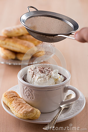 Chokladkopp med piskade kräm och sockerkaksbit i form av ett finger