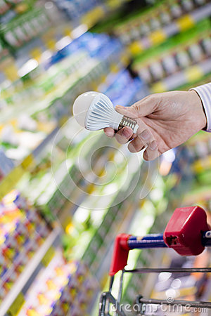 Choosing energy efficient lighting: closeup on male or female hand holding or selecting LED diode light bulb lamp in DIY store
