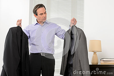 Choosing a suit for meeting. Mature businessman standing with a