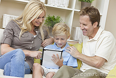 Chłopiec komputerowej rodziny rodziców syna pastylki używać