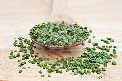 Chopped chives on wooden serving spoon