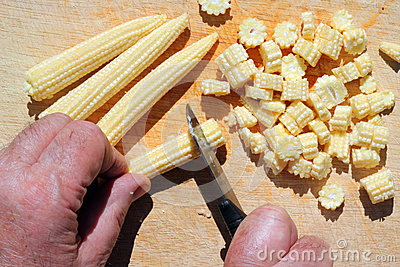 Chopping organic baby corn.