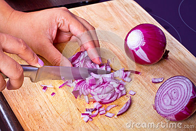 Chopping red onion in kitchen