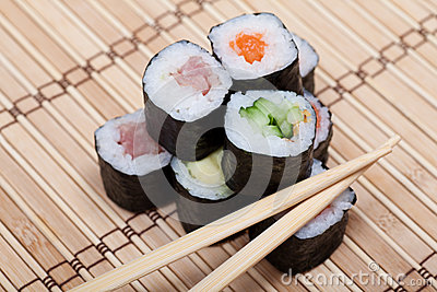 Chopsticks and sushi on bamboo mat