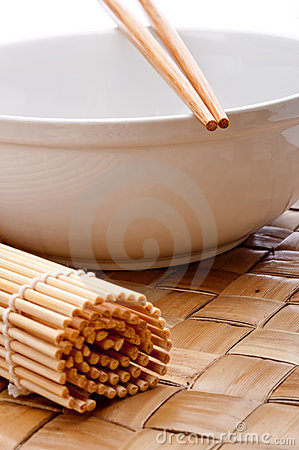 Chopsticks on a white bowl with a sushi mat