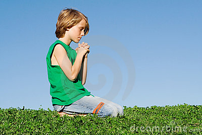 Christian child kneeling praying
